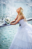 Happy bride with bouquet of flower near fountain Royalty Free Stock Photos