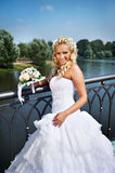 Happy bride with bouquet of flower near lake Stock Image
