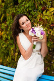 Happy bride with a bouquet idit in the park. Royalty Free Stock Image