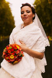 Happy bride with bouquet in white stole Royalty Free Stock Images