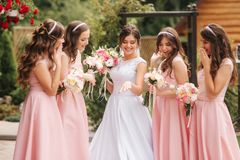 Happy bride with bridesmaid hold bouquets and have fun outside. Beautiful bridesmaid in same dresses stand by the. Charming bride in long wedding dress royalty free stock images
