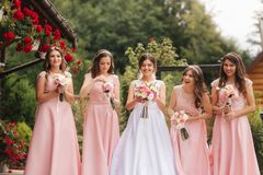 Happy bride with bridesmaid hold bouquets and have fun outside. Beautiful bridesmaid in same dresses stand by the. Charming bride in long wedding dress royalty free stock photography