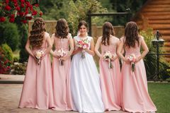 Happy bride with bridesmaid hold bouquets and have fun outside. Beautiful bridesmaid in same dresses stand by the. Charming bride in long wedding dress stock images