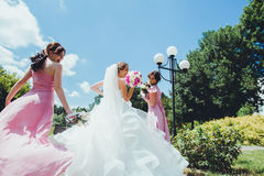 Happy Bride with bridesmaids in the park on the wedding day Royalty Free Stock Images