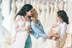 Happy bride and bridesmaids trying on dresses royalty free stock images