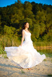 Bride standing at the riverside under sunset outdoors Stock Photo