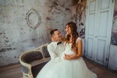 Happy bride with dark blonde long hair sits on groom& x27;s knees stock photo