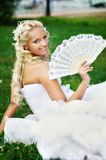 Happy bride with fan on grass Stock Photography