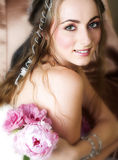 Happy bride with flowers. Beautiful happy young bride with long brown hair holding  pink spring flowers and wearing antique and vintage accessories Stock Images