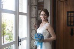 Happy bride in front of window Stock Photo