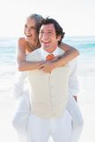 Happy bride getting a piggy back from handsome husband Stock Photos