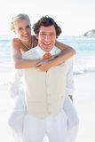Happy bride getting a piggy back from husband Royalty Free Stock Photos
