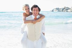 Happy bride getting a piggy back from husband smiling at camera Royalty Free Stock Images