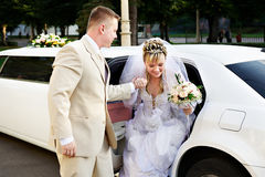Happy bride and groom. Out of wedding limousine Stock Photography