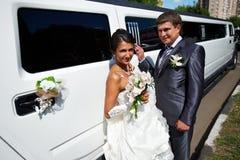 Happy bride and groom. Near wedding limo Royalty Free Stock Photos