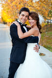 Happy bride and groom. At a park on their wedding day royalty free stock photo
