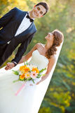 Happy bride and groom. At a park on their wedding day stock photography