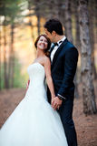 Happy bride and groom. At a park on their wedding day stock photo