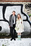 Happy bride and groom against a wall with graffiti Stock Photography