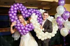 Happy bride and groom with air balloons. Happy bride and groom with purple and white balloons Stock Photography