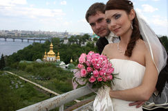 Happy bride and groom. On background of church. She is holding roses bouquet Royalty Free Stock Image