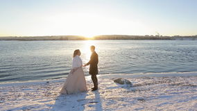 Happy bride and groom bathe in rays of setting sun on coast of river in winter. Camera move to couple standing near pond. Young handsome tall man in white long stock footage
