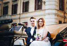 Happy bride and groom in beautiful carriage on wedding walk.  Stock Photography