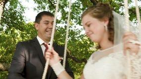 Happy bride and groom in beautiful white dress swinging on swing in summer park. Swing on branch of an oak in summer stock video