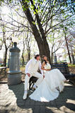Happy bride and groom on bench Stock Photo