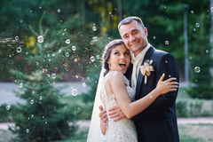 Happy bride and groom and blowing bubbles in park Royalty Free Stock Photos