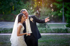 Happy bride and groom and blowing bubbles in park Stock Images