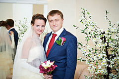 Happy bride and groom with bouquet Stock Images