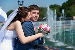 Happy bride and groom with bouquet at wedding walk Stock Images
