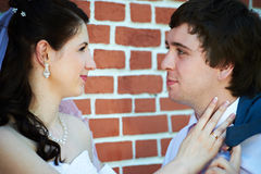 Happy bride and groom about brick wall Stock Images