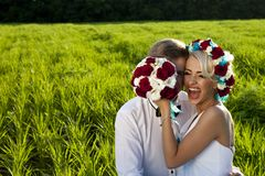Happy bride and groom on the bright green field Royalty Free Stock Images
