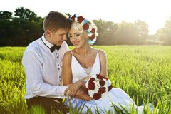 Happy bride and groom on the bright green field Royalty Free Stock Photos