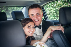 Happy bride and groom in the car Stock Photography