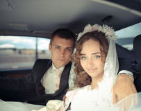 Happy bride and groom in a car Royalty Free Stock Photography