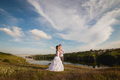Happy bride and groom celebrating wedding day. Married couple on beautiful landscape Stock Photography