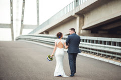 Happy bride and groom celebrating wedding day. Married couple going away on bridge. Long family life road concept. Royalty Free Stock Image