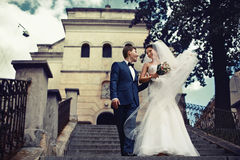 Happy bride and groom come down from a church Royalty Free Stock Images