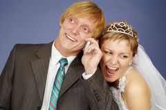 Happy bride and groom is congratulated by phone Royalty Free Stock Images