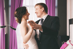 Happy bride and groom dancing in bedroom Royalty Free Stock Photography