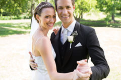 Happy bride and groom dancing together in garden. Portrait of happy bride and groom dancing together in garden Stock Image