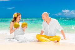 Happy bride and groom drink coconut water and having fun on a tr Royalty Free Stock Image