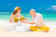 Happy bride and groom drink coconut water and having fun on a tr Stock Photo