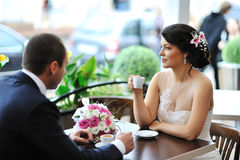 Happy bride and groom drinking coffee at an outdoor cafe Stock Photo