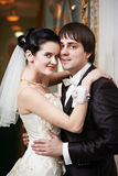 Happy bride and groom embrace stock image