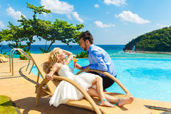 Happy bride and groom enjoy a cocktail poolside infinity. Tropic Royalty Free Stock Images