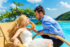 Happy bride and groom enjoy a cocktail poolside infinity. Tropic Royalty Free Stock Image